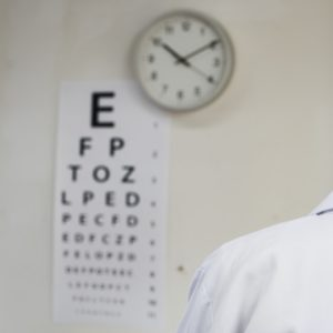 Doctor wearing lab coat standing in front of eye test chart