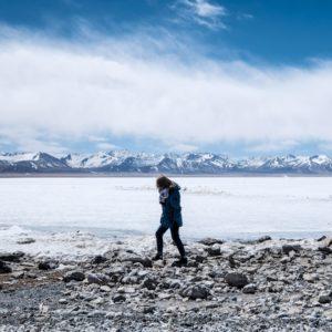 Women walking next to frozen lake during winter