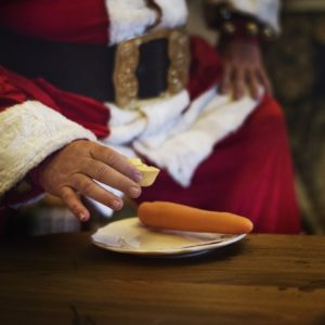 Santa Claus by the fire reaching out for a plate with a carrot on it