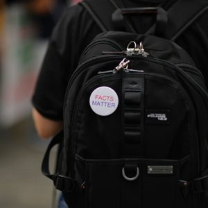 """Teen carrying backpack with a """"Facts Matter"""" button pinned to it"""