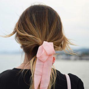 Women looking at ocean wearing pink ribbon in hair