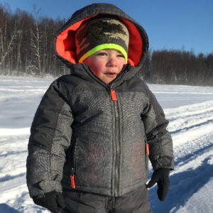 Young boy in winter clothing out in a field of snow