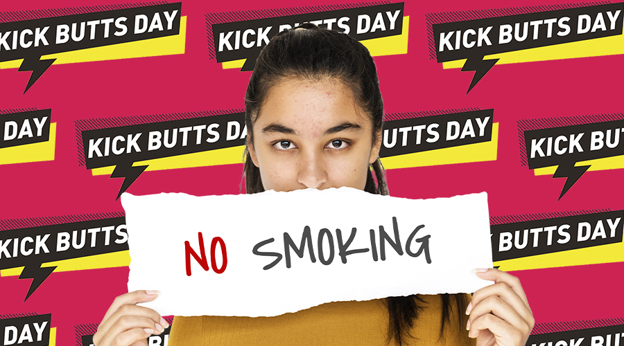 Woman holding no smoking sign in front of Kick Butts Day background