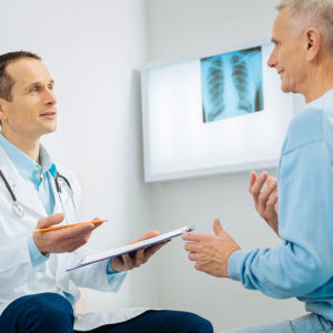 Middle age male doctor holding a clipboard and talking with older male patient with an x-ray film pinned to a wall-mounted box light