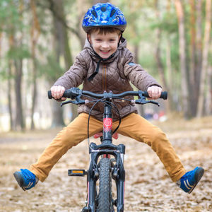 Young boy riding bicycle in the forest.