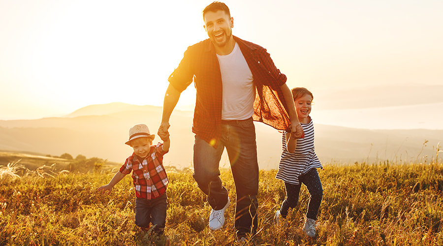 Father with a goatee holding the hands of his two young children, a toddler-aged boy and elementary school-aged girl, while running though a hilly field in the morning.