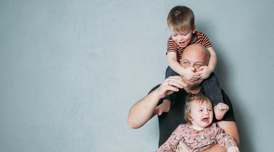 Father looking glum while carrying to two crying toddlers, a boy on his shoulders and a girl in his arms.