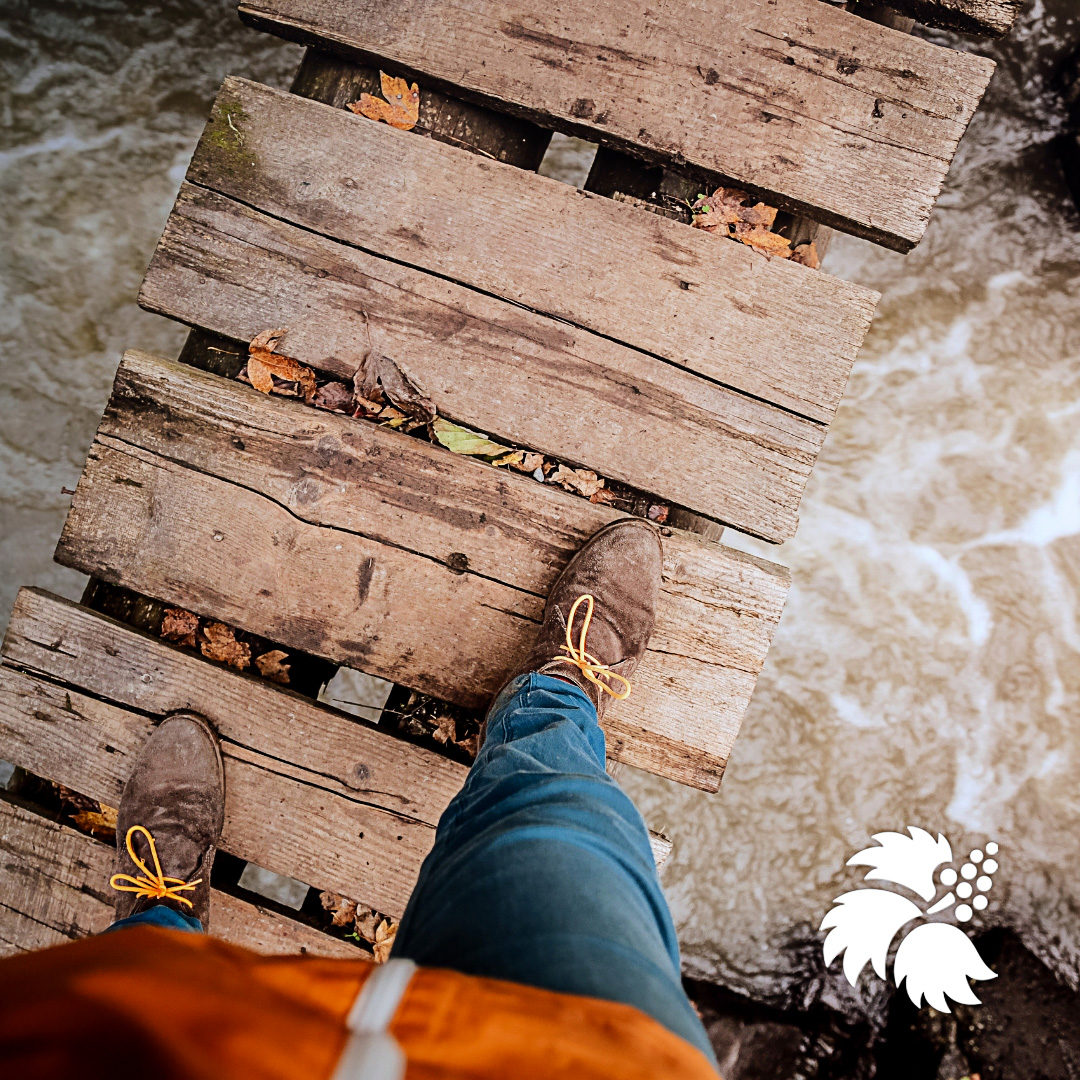 person stepping across small wood bridge over a stream