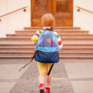 Young boy with school backpack walking towards school entrance steps