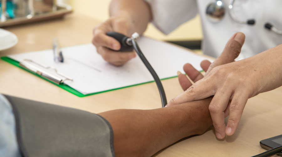 A pair of doctor's hands is using a blood pressure cuff on a patient's arm on table with a clipboard and pen.