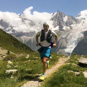 Man dressed in running gear trekking across a hill path with a cloud-covered mountain range in the background.