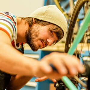 Young bearded man tuning up his bike in a workshop.