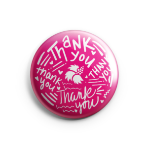 "Pink-colored ""Thank You"" pin with white text showcasing hand-drawn fonts."