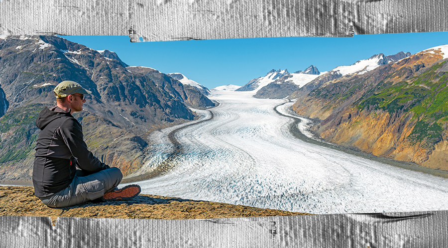 Man wearing a cap and sunglasses, sitting cross-legged on a hilltop, looking over a snow-covered valley. The photo has duct-taped border edges.