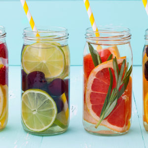 Four different fruit-infused glasses of water with a variety of fruits and topped with yellow-striped straws.