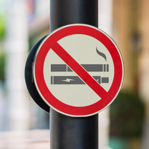 "A ""no smoking"" street sign that features cigarettes and a vaping device."