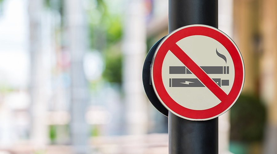 """A """"no smoking"""" street sign that features cigarettes and a vaping device."""