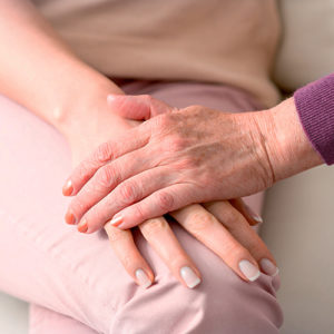 Two woman holding hands in a comforting manner.