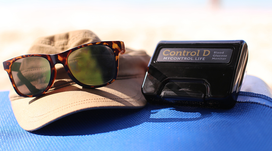 Hat, sunglasses and blood sugar monitoring device sitting on a blue bag.