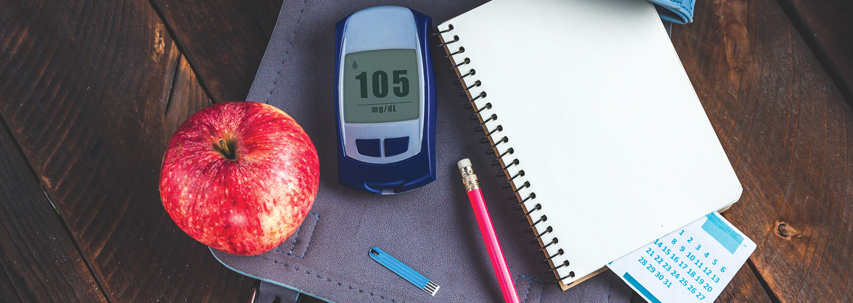 Diabetes management gear sitting on a table next to an apple.