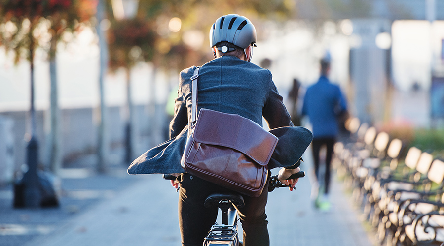Man biking in a suit, carrying a legal briefcase.