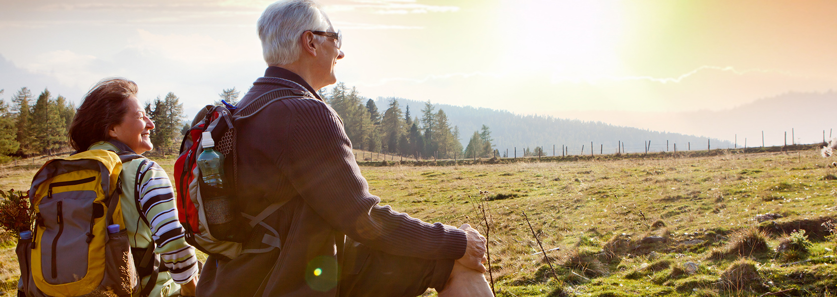 Two senior citizen hikers are sitting with backpacks looking out to an open field.